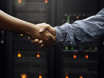 Why You Need a Turnkey Data Center Partner | Image of two arms shaking hands in front of server racks